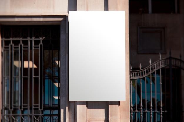 Rechthoekig wit muuraanplakbord dichtbij de metaalpoort Gratis Foto