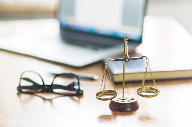 Rechtvaardigheidsschaal en bril op houten bureau in rechtszaal Gratis Foto