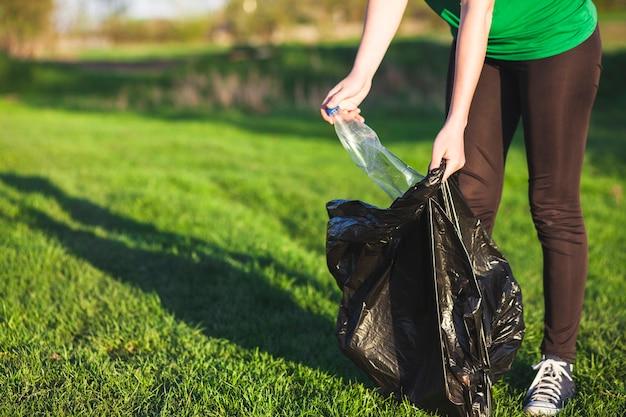 Recycleer concept met vrouw die afval verzamelt Gratis Foto