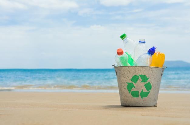 Recycleer, mand met plastic fles op het strand Premium Foto