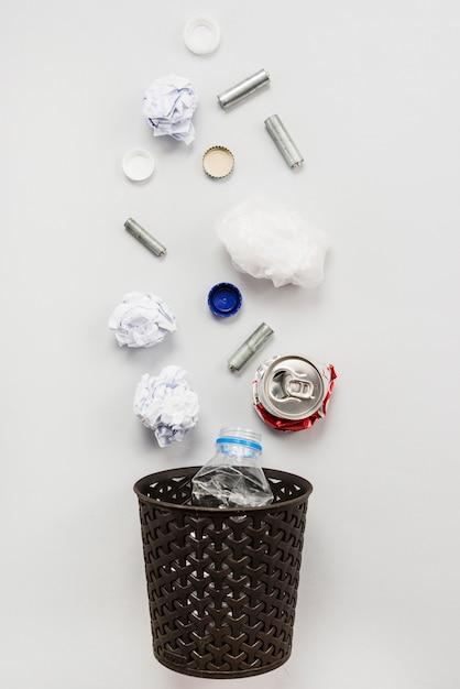 Recycleerbare afvalvoorwerpen die in vuilnisbak vallen Gratis Foto