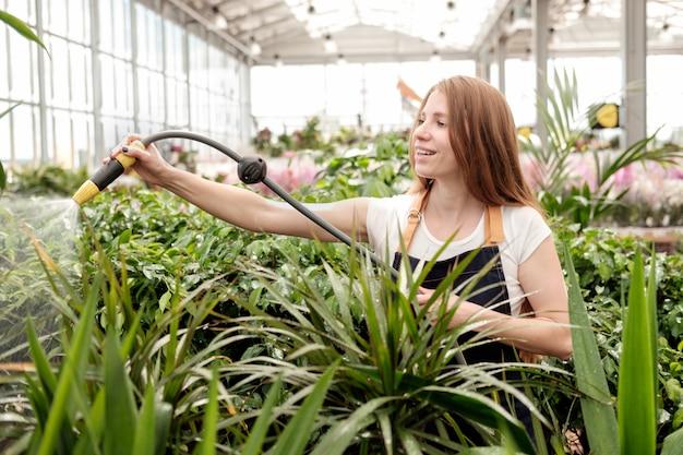 Redhead jonge vrouwenarbeider in de serre gietende installaties van de installatiemarkt en het glimlachen Premium Foto