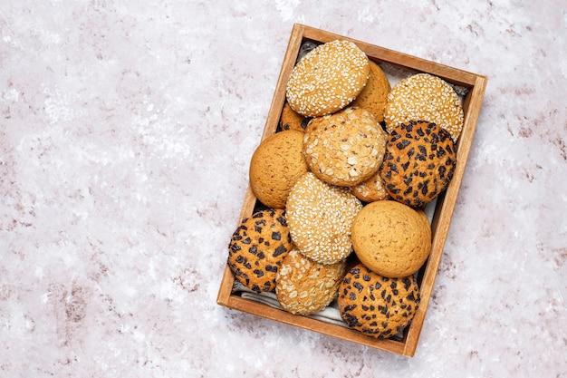 Reeks diverse amerikaanse stijlkoekjes in houten dienblad op lichte concrete achtergrond. zandkoek met sesamzaad, pindakaas, havermout en chocoladeschilferkoekjes. Gratis Foto