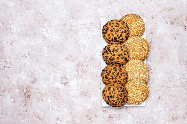 Reeks diverse amerikaanse stijlkoekjes op een lichte concrete achtergrond. zandkoek met confetti, sesamzaad, pindakaas, havermout en chocoladeschilferkoekjes. Gratis Foto