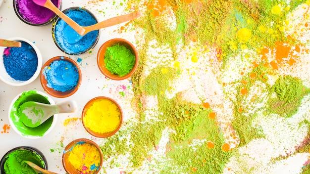 Reeks kommen met heldere droge kleuren dichtbij stapels kleuren Gratis Foto
