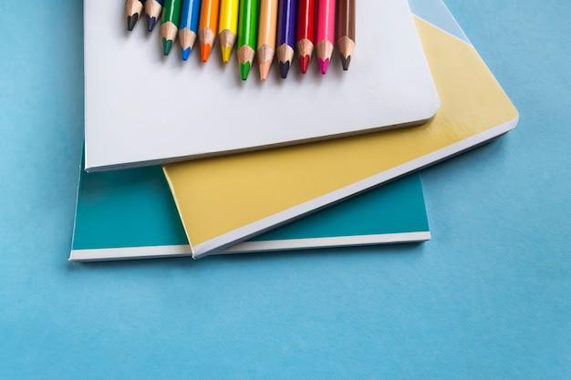 Reeks oefenboeken en kleurpotloden op een groene achtergrond met ruimte voor tekst. school accessoires. plat leggen Premium Foto