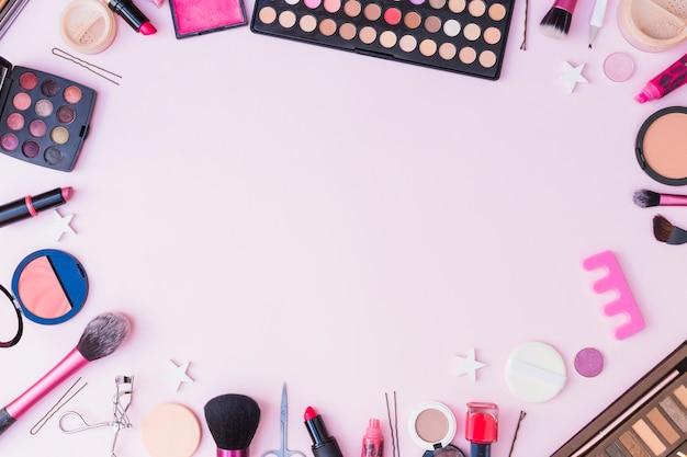 Reeks schoonheidsmiddelenproducten die kader op roze achtergrond vormen Gratis Foto