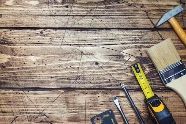 Reeks verschillende reparatiehulpmiddelen op houten achtergrond met exemplaarruimte. Premium Foto