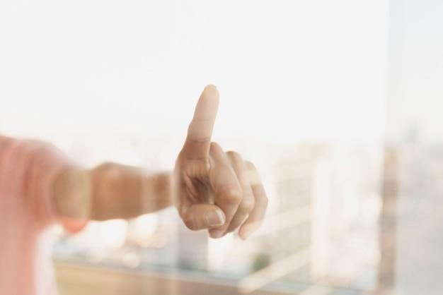 Reflectie van wijzende vinger op venster Gratis Foto