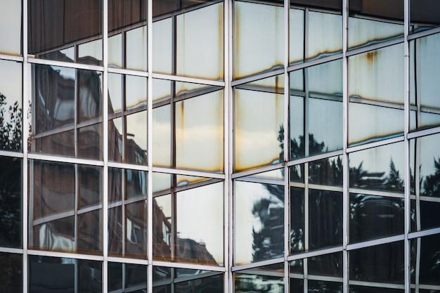 Reflecties op de hoek van de glazen gevel van een kantoorgebouw Premium Foto