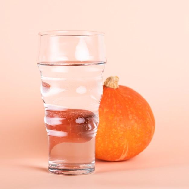 Regeling met groot glas water en pompoen Gratis Foto