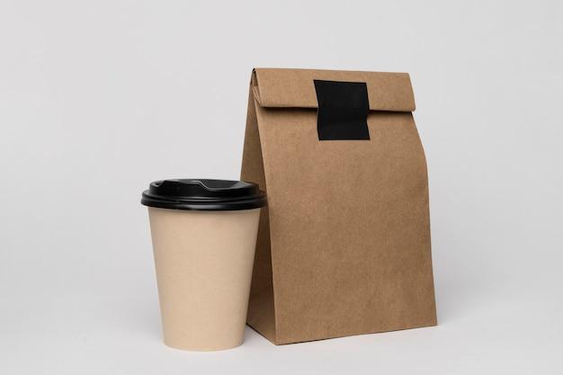 Regeling met koffiekopje en papieren zak Gratis Foto