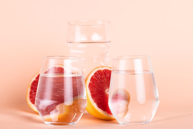 Regeling met waterglazen en rode sinaasappels Gratis Foto