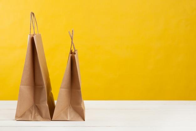 Regeling van boodschappentassen op fel gele achtergrond Premium Foto