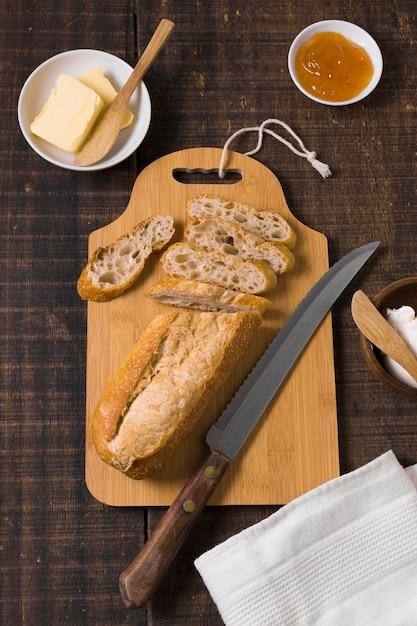 Regeling van brood en ingrediënten op een houten bord Gratis Foto