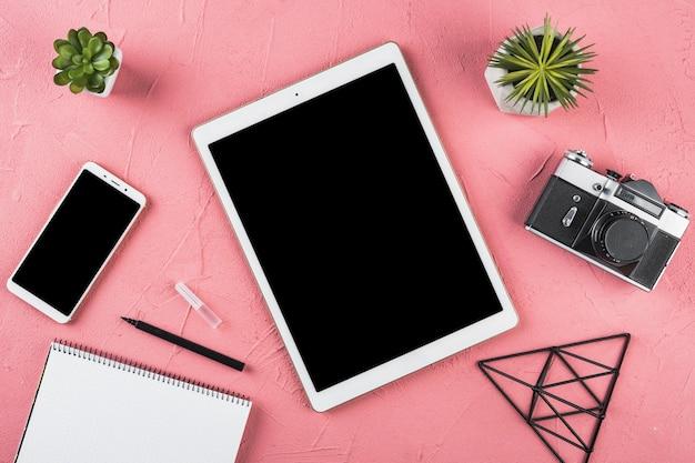 Regeling van bureauelementen op roze achtergrond Gratis Foto