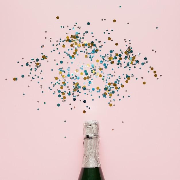 Regeling van champagnefles en kleurrijke confetti Gratis Foto
