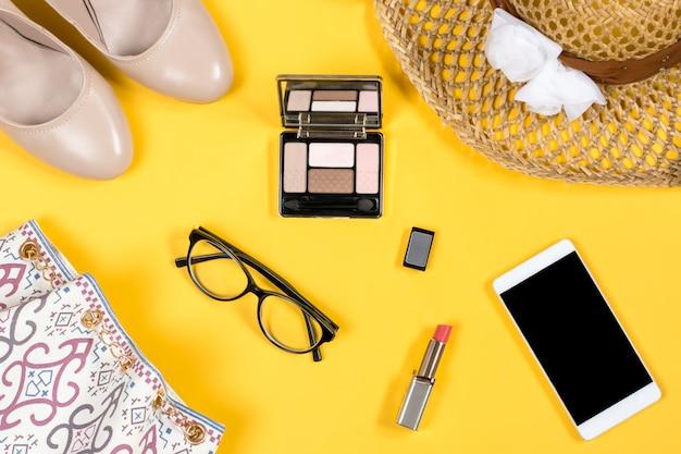 Regeling van de essentiële accessoires van de vrouwenzomer op heldere gele achtergrond Premium Foto