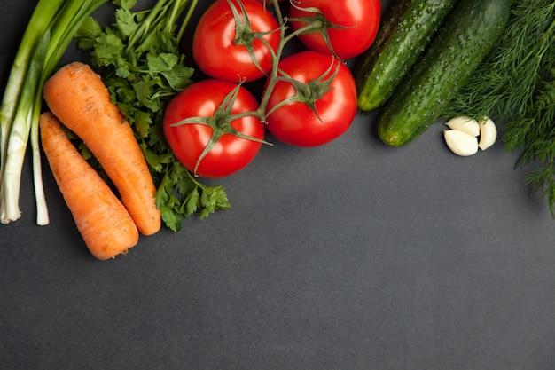Regeling van gemengde kleurrijke groenten, geïsoleerd op donkere grijze leisteen achtergrond met lege kopie ruimte. banier Premium Foto