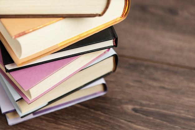 Regeling van kleurrijke boeken op houten tafel Gratis Foto