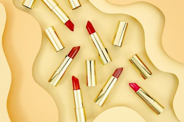 Regeling van kleurrijke lippenstiften met abstracte achtergrond Gratis Foto