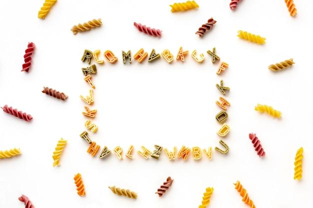 Regeling van ongekookt kleurrijk fusilli en alfabetpastakader Gratis Foto