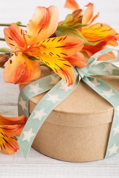Regeling van oranje lelie bloemen en geschenkdoos Premium Foto