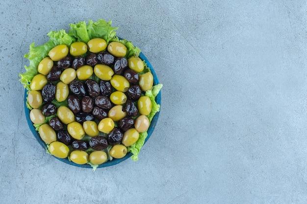 Regeling van pitloze olijven op een met sla overdekte schotel op marmeren tafel. Gratis Foto
