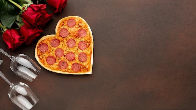 Regeling voor valentijnsdag met hartvormige pizza en kopie ruimte Gratis Foto