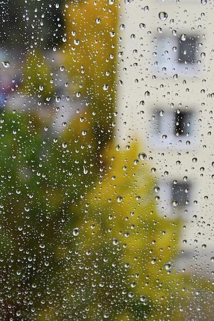 Regen. herfst seizoensgebonden achtergrond met regen druppels op het venster. Gratis Foto
