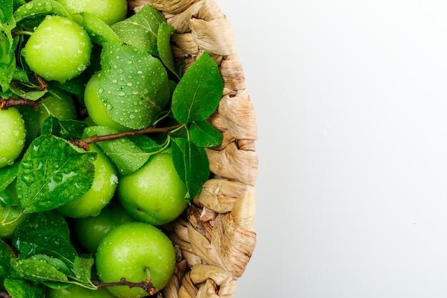 Regenachtige groene pruimen in een rieten mand met bladeren close-up op een witte muur Gratis Foto