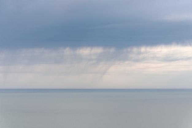Regenachtige wolken boven een kalme zee, strook regen op horizon, zachte focus, lange blootstelling, abstract zeegezicht. Premium Foto