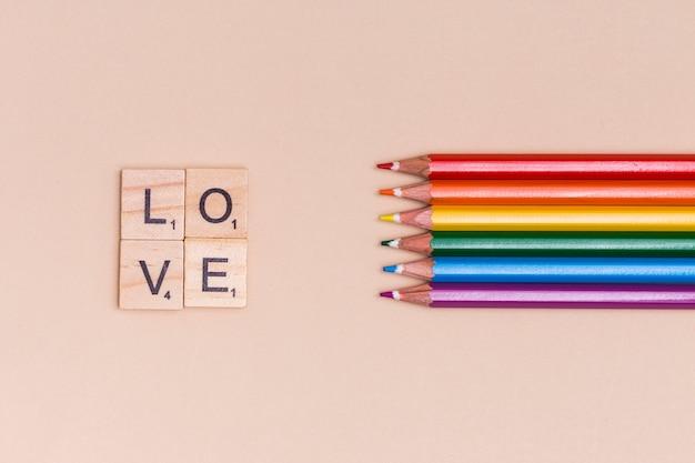 Regenboog kleurrijke potloden en liefdebrieven op beige achtergrond Gratis Foto