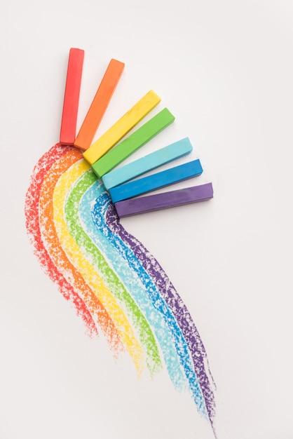 Regenbooggradiënt gemaakt van pastelkrijt krijt over de kleurrijke sporen Gratis Foto