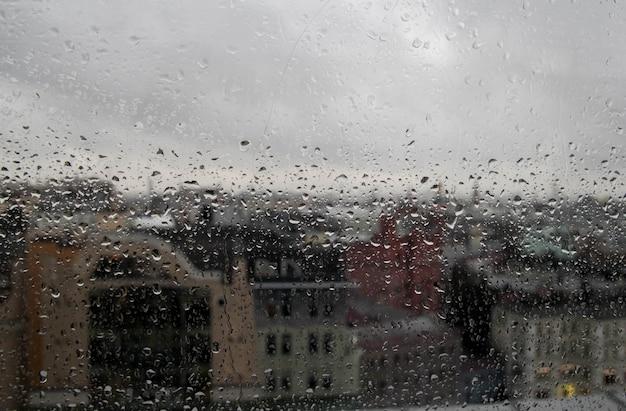 Regendaling op helder glasvenster, weerspiegeling van vage stad en hemel, licht bokeh van buitenaf Premium Foto