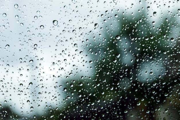 Regendalingen op venster, regenachtige dag. dalingen op de straatregen van de glasvenstertextuur. Premium Foto