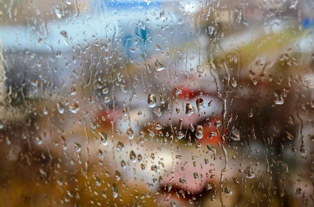 Regendruppels op de achtergrond van het straatvenster Premium Foto