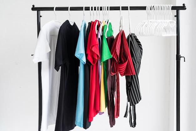Reinig verschillende t-shirts en schortkleding die na het wassen aan het rek hangt. Premium Foto