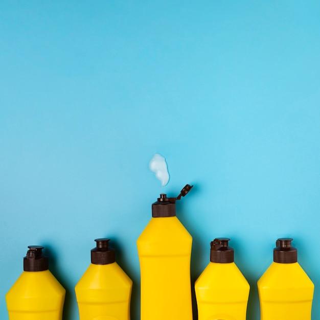 Reiniging concept met gele wasmiddel flessen Gratis Foto