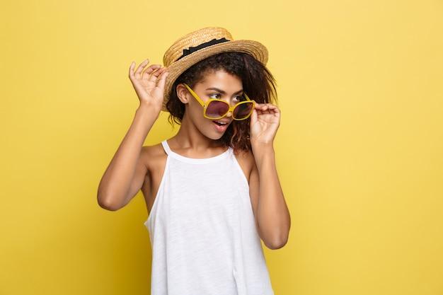 Reis concept - close-up portret jonge mooie aantrekkelijke afrikaanse amerikaanse vrouw met trendy hoed lachend en blije uitdrukking. gele pastelstudio achtergrond. kopieer de ruimte. Gratis Foto