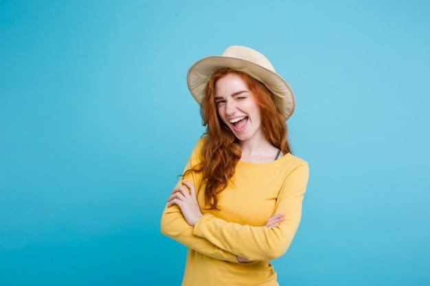 Reis concept - close-up portret jonge mooie aantrekkelijke roodharige meisje wtih trendy hoed en zonnebril lachend. blauwe pastelachtergrond. kopieer de ruimte. Gratis Foto