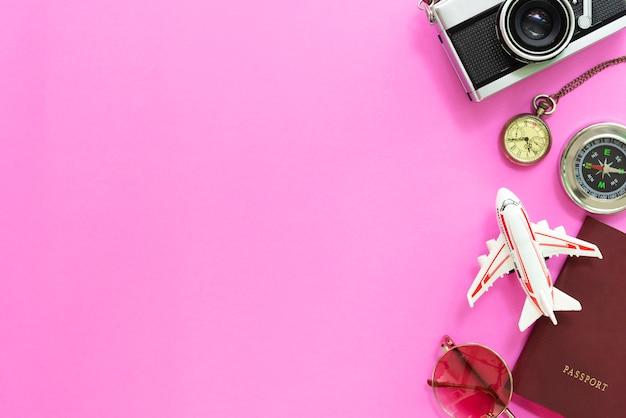 Reis- en zomertijd concept. plat leggen van accessoires en camera op roze achtergrond. Premium Foto