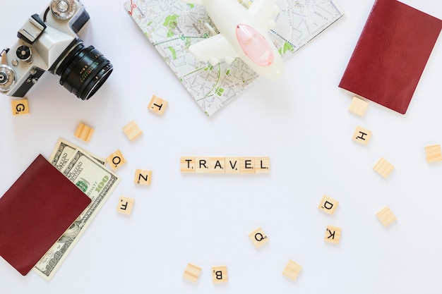 Reis houten blokken; camera; kaart; bankbiljetten; paspoort en vliegtuig op witte achtergrond Gratis Foto
