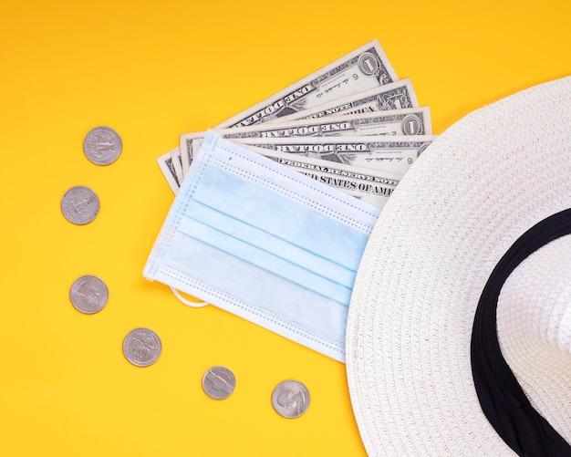 Reis in 2020 met maskergeld hoedmunten gele achtergrond, er zijn er niet meer voor covid-19 Premium Foto