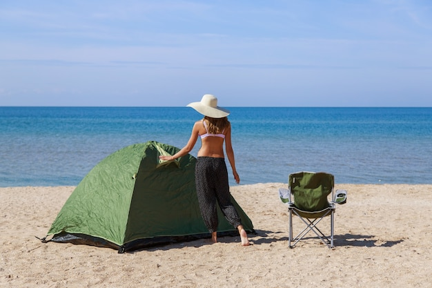 Reis naar de zee. kamperen op het strand. vakantie aan het water. mannen en een tent met een toeristenstoel op het zand Premium Foto