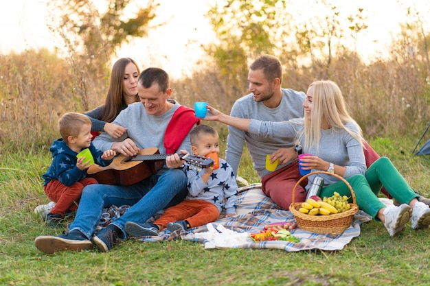 Reis, toerisme, stijging, picknick en mensenconcept - groep gelukkige vrienden met tent en dranken die gitaar spelen bij het kamperen Premium Foto