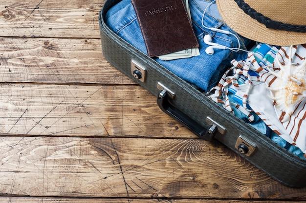 Reis voorbereidingen concept met koffer, kleding en accessoires op een oude houten tafel. bovenaanzicht ruimte kopiëren Premium Foto