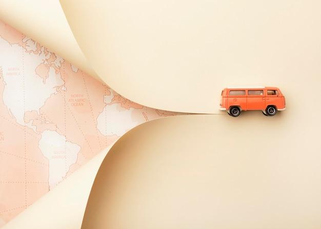 Reisconcept met wereldkaart en speelgoedbusje Gratis Foto