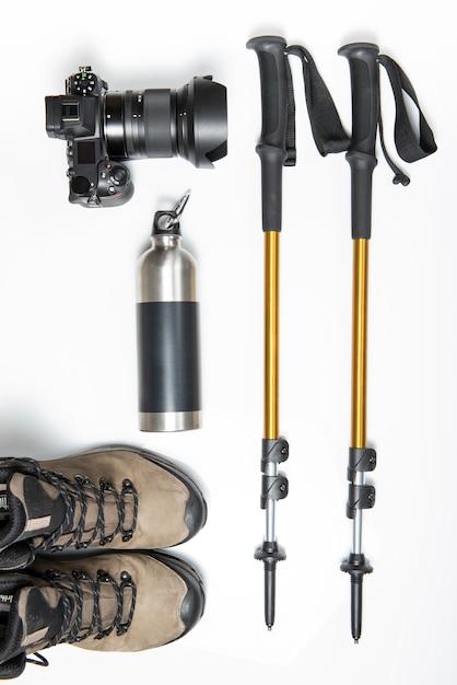 Reisfotografie kit. een paar wandel- of trekkingstokken stokken, camera, fles en trekking laarzen geïsoleerd op Premium Foto