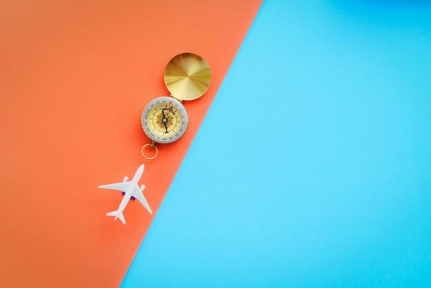 Reisoppervlakconcept vliegtuigreizigersvlieg met passagiersvliegtuig en kompas op blauw en oranje Premium Foto